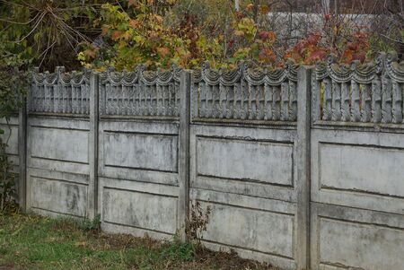 part private concrete gray fence on a rural street in the grass
