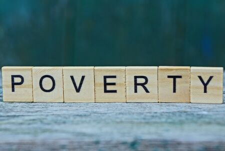 the word poverty from wooden letters on a gray table on a green background
