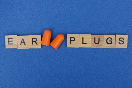 red plastic ear plugs and word made of wooden letters on a blue table