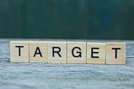 word target made of brown wooden letters on a gray table Stok Fotoğraf