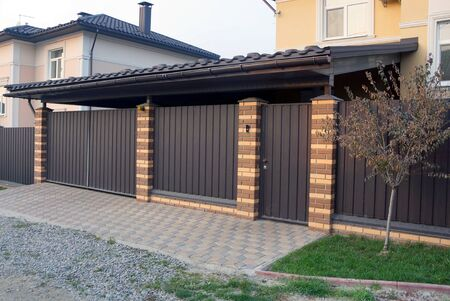 brown gate and part fence made of metal and bricks outside