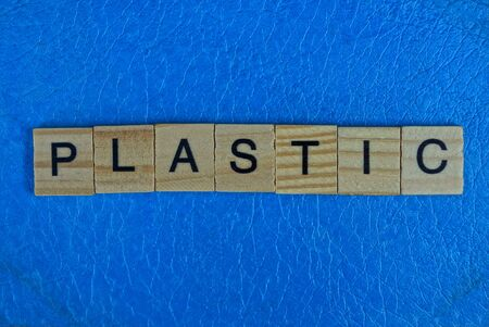 the word from wooden letters lies on a piece of blue plastic