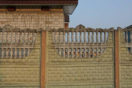 part concrete brown fence on a rural street Stok Fotoğraf