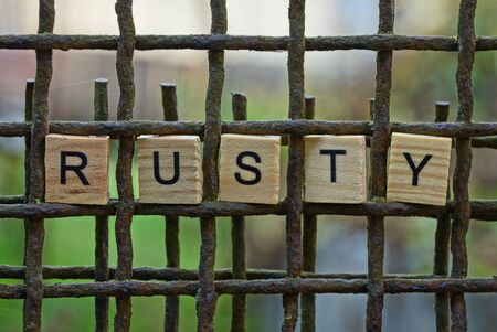 word rusty made of wooden letters on an iron brown grate Stok Fotoğraf