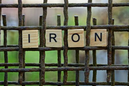 word iron made of wooden letters on an rusty brown grate