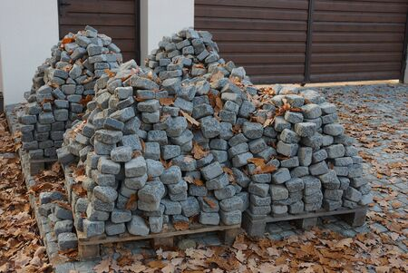 pile of gray stone paving tiles in dry leaves on the street Stok Fotoğraf