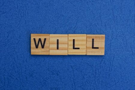 word will of brown wooden letters on a blue table