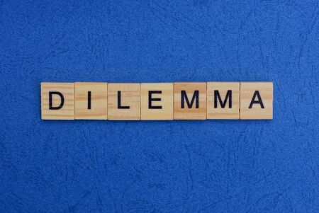 word dilemma made of wooden letters on a blue table