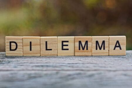 word dilemma made of wooden letters on a gray table Stok Fotoğraf