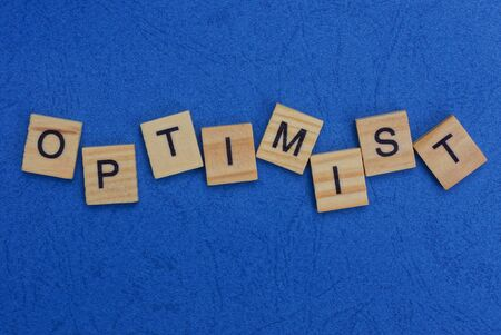 word optimist made of wooden letters on a blue table Stok Fotoğraf