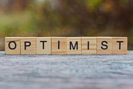 word optimist made of wooden letters on a gray table
