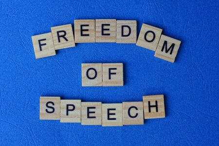 phrase freedom of speech from wooden letters on a blue table