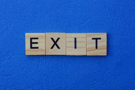 word exit made from brown wooden letters lies on a blue table Stok Fotoğraf