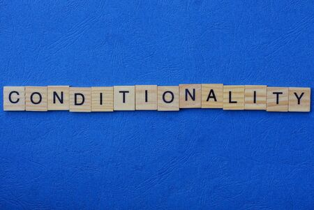 word conditionality of brown wooden letters on a blue table Stok Fotoğraf