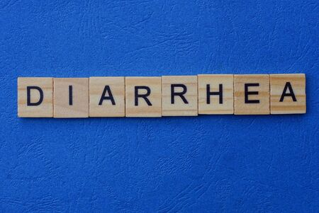 the word diarrhea from brown wooden letters lies on a blue table