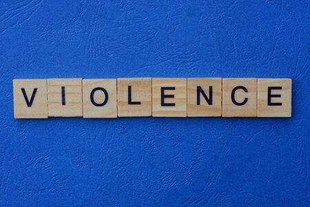 word violence made of brown wooden letters on a blue table Stok Fotoğraf