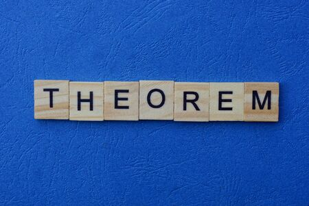 The word theorem made of brown wooden letters lies on a blue table Фото со стока