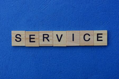 word service made of wooden brown letters on a blue background Stok Fotoğraf