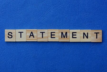 word statement made from brown wooden letters on a blue table Stok Fotoğraf