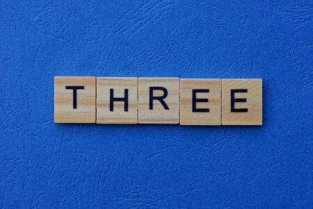 word three made of wooden brown letters on a blue background Stok Fotoğraf