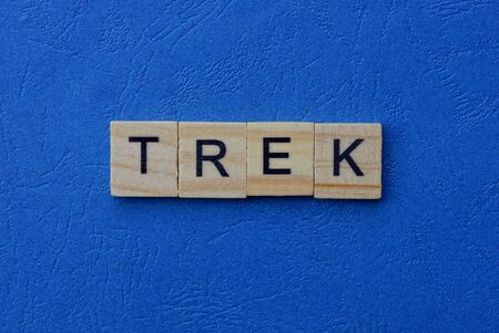 word trek made of brown wooden letters on a blue table