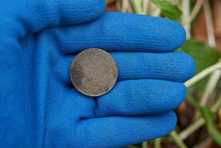 old copper coin lies on the palm of a hand in a blue glove Stok Fotoğraf