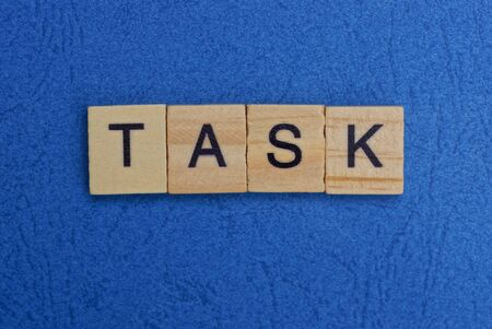 word task made of brown wooden letters on a blue table
