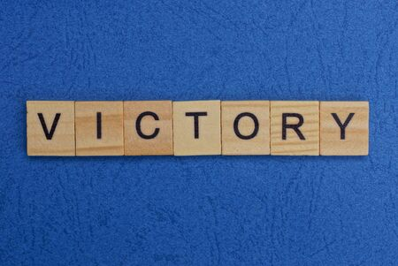 word victory made of brown wooden letters on a blue table