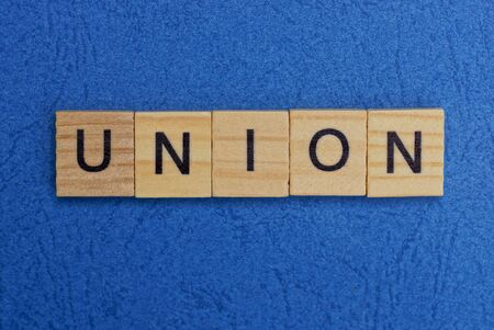 word union made of brown wooden letters on a blue table Stok Fotoğraf