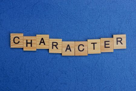 word character made of brown wooden letters on a blue table Stok Fotoğraf