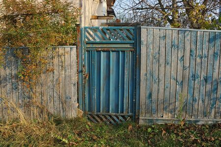 old blue metal door and gray wooden fence in green grass on a rural street 스톡 콘텐츠