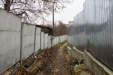 passage in an alley with a path between a metal and concrete fence 스톡 콘텐츠