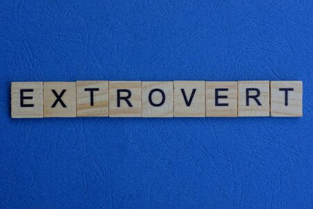 word extrovert from brown wooden letters lies on a blue table Stock Photo