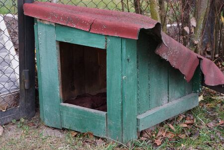 empty green doghouse from wooden boards on the street near the fence