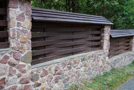 fence of brown wooden boards and a stone foundation in green grass