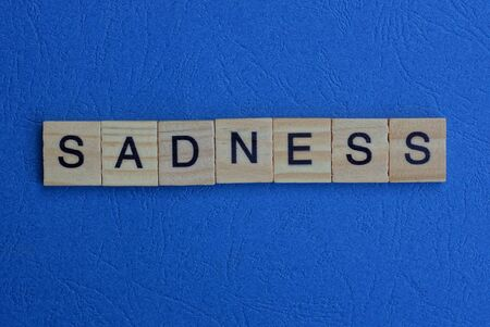 The word sadness from brown wooden letters lies on a blue table Stock Photo