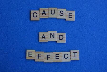 die Phrase Ursache und Wirkung von braunen Holzbuchstaben liegt auf einem blauen Tisch