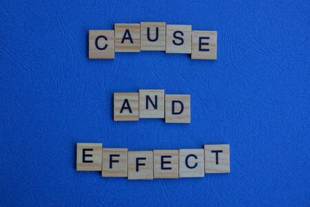 the phrase cause and effect of brown wooden letters lies on a blue table
