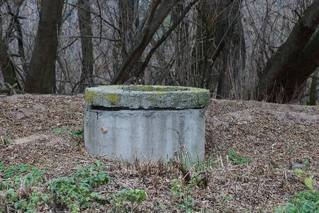 old gray concrete sewer stands in dry grass on nature Фото со стока