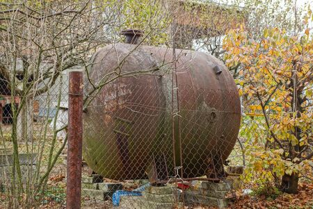 one brown rusty iron tank behind a fence in the vegetation