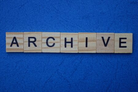 word archive made from brown wooden letters lies on a blue background