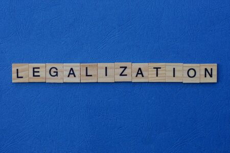 word legalization made from gray wooden letters lies on a blue background