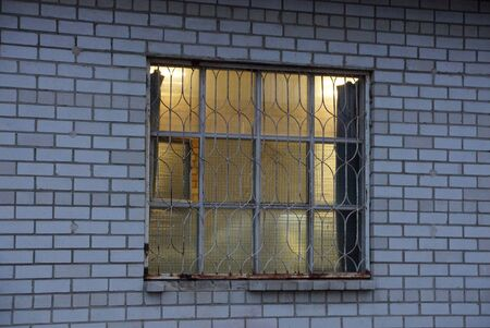 yellow light in a large window behind an iron bars on a gray brick wall