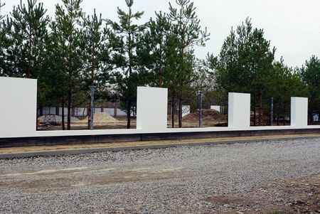 white unfinished concrete fence on the street by the road in front of pine trees 스톡 콘텐츠