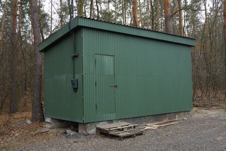 a large iron green trailer with a door stands among pine trees in a park