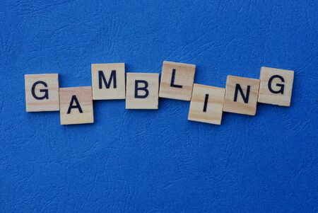 word gambling made from gray wooden letters lies on a blue background