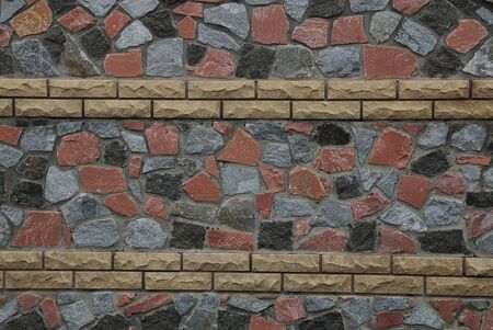 texture of colored stones and cobblestones with brown bricks in the fence wall