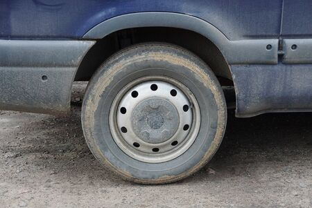 one gray dirty wheel on a blue car stands on the asphalt of the road