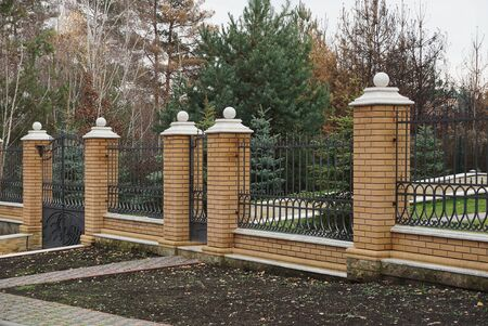 part of the fence on the street of brown bricks and black iron bars