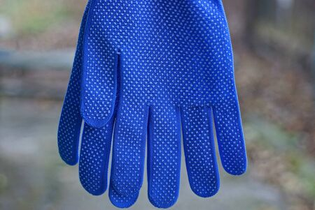 two blue work gloves hanging against a gray background